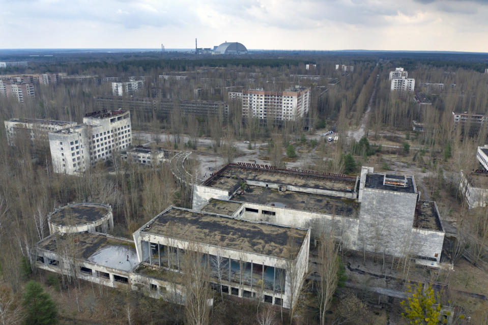 A view of the ghost town of Pripyat with a shelter covering the exploded reactor at the Chernobyl nuclear plant in the background, Ukraine, Thursday, April 15, 2021. The vast and empty Chernobyl Exclusion Zone around the site of the world's worst nuclear accident is a baleful monument to human mistakes. Yet 35 years after a power plant reactor exploded, Ukrainians also look to it for inspiration, solace and income. (AP Photo/Efrem Lukatsky)