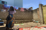 """Reby hangs laundry outside her home in Beni, eastern Congo, on Saturday, May 1, 2021. In 2019, she met World Health Organization Dr. Boubacar Diallo, of Canada, when he came into a mobile phone shop where she was working. He asked her to talk about """"important things"""" with him in a hotel and gave her $100 for """"transport costs,"""" she told the AP. """"My God, a beautiful girl like you who gets $60 a month is not enough,"""" he said, according to Reby. """"You are a big girl and if you sleep with me, you are going to be a high-ranking member of the Ebola response in Beni and you are going to receive around $800 a month."""" She said she refused Diallo's offer, but continued to see him when he came into her shop. """"From that day on, he always called me the difficult girl,"""" she said. (AP Photo/Kudra Maliro)"""