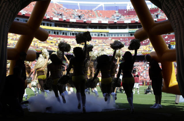 "In this Aug. 24, 2013 photo, <a class=""link rapid-noclick-resp"" href=""/nfl/teams/was/"" data-ylk=""slk:Washington Redskins"">Washington Redskins</a> cheerleaders run out of a tunnel before an NFL preseason football game. (AP)"