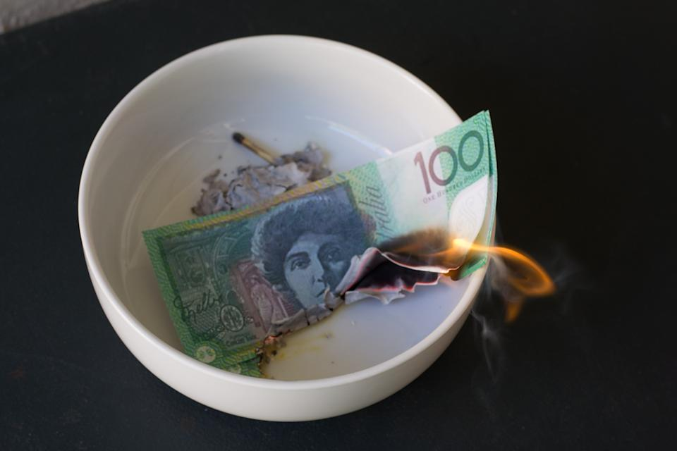 $100 note burning in a bowl