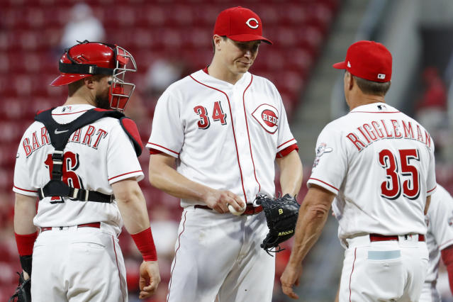 Cincinnati Reds starting pitcher Homer Bailey (34) is relieved by interim manager Jim Riggleman (35) alongside catcher Tucker Barnhart (16) in the sixth inning of the team's baseball game against the Pittsburgh Pirates, Wednesday, May 23, 2018, in Cincinnati. (AP Photo/John Minchillo)