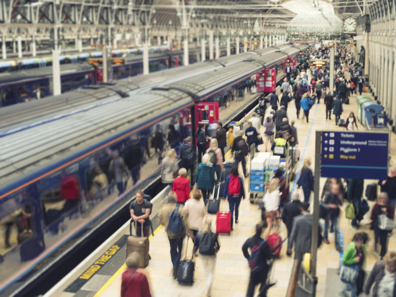 Horizontal color image of a busy railroad platform at Paddington station in London, UK.