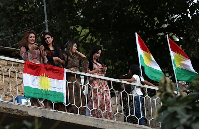 <p>Iraqi Kurdish woman stand next to Kurdish flags during a gathering on Sept. 10, 2017, to show support for the upcoming independence referendum and encourage people to vote in the town of Akra, some 300 miles north of Baghdad. (Photo: Safin Hamed/AFP/Getty Images) </p>