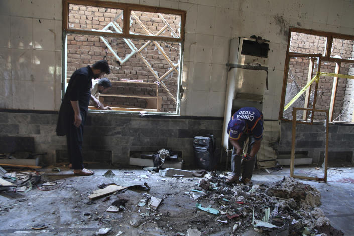 Pakistani rescue workers examine the site of a bomb explosion in an Islamic seminary, in Peshawar, Pakistan, Tuesday, Oct. 27, 2020. A powerful bomb blast ripped through the Islamic seminary on the outskirts of the northwest Pakistani city of Peshawar on Tuesday morning, killing some students and wounding dozens others, police and a hospital spokesman said. (AP Photo/Muhammad Sajjad)
