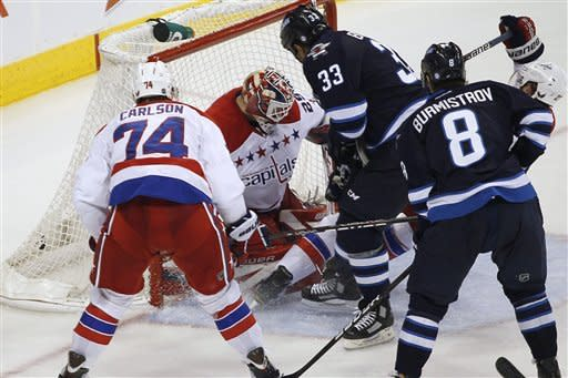 Winnipeg Jets' Dustin Byfuglien (33) scores the game-winning goal against Washington Capitals goaltender Tomas Vokoun (29) as John Carlson (74) defends during the third period of an NHL hockey game in Winnipeg, Manitoba, on Friday, March 16, 2012. (AP Photo/The Canadian Press, John Woods)
