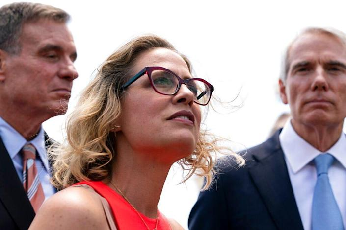 Sen. Kyrsten Sinema, D-Ariz., center, Sen. Mark Warner, D-Va., left, and Sen. Rob Portman, R-Ohio, speak with reporters upon arriving at the Capitol after a meeting with President Joe Biden at the White House in Washington, Thursday, June 24, 2021. A bipartisan group of lawmakers have negotiated a plan to pay for an estimated $1 trillion compromise plan. (AP Photo/Alex Brandon)