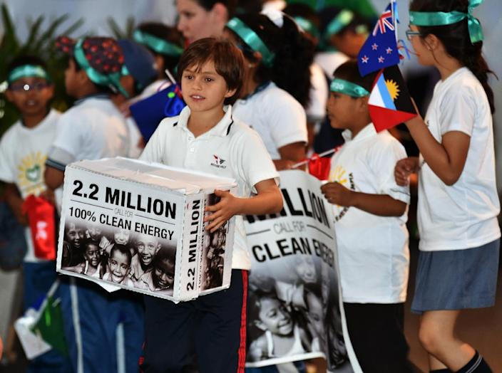 A boy carries a symbolic box representing 2.2 million signatures of people who call for environmentally friendly attitudes during the COP20 and CMP10 climate conferences in Lima on December 10, 2014 (AFP Photo/Cris Bouroncle)