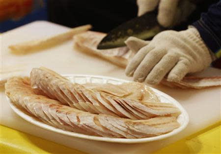 A fish dealer slices frozen pollack at his store at a market in central Seoul September 13, 2013. REUTERS/Lee Jae-Won