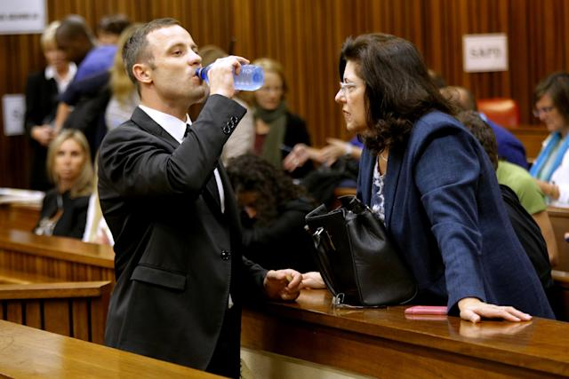Oscar Pistorius drinks water in court in Pretoria, South Africa, Friday, March 14, 2014, prior to his tenth day in court. Pistorius is charged with the shooting death of his girlfriend Reeva Steenkamp, on Valentines Day in 2013. (AP Photo/Kim Ludbrook, Pool)