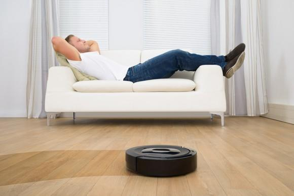 A man reclining on a couch as a robotic vacuum cleans the floor.