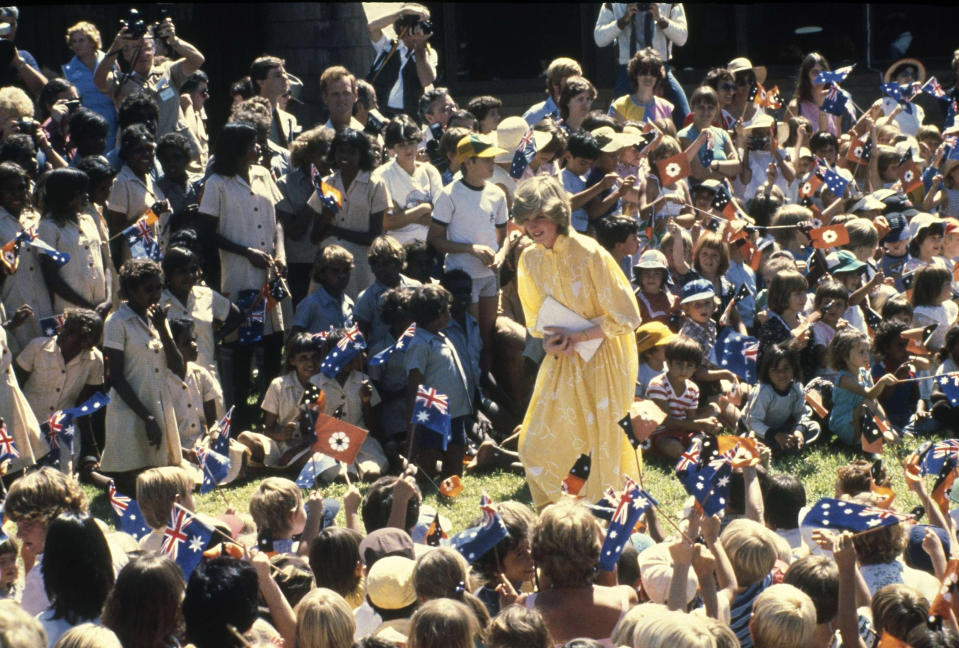 """FILE - In this March 21, 1983 file photo, Diana, Princess of Wales is pictured amid a large group of schoolchildren during her visit to Alice Springs, Australia. For someone who began her life in the spotlight as """"Shy Di,"""" Princess Diana became an unlikely, revolutionary during her years in the House of Windsor. She helped modernize the monarchy by making it more personal, changing the way the royal family related to people. By interacting more intimately with the public -- kneeling to the level of children, sitting on edge of a patient's hospital bed, writing personal notes to her fans -- she set an example that has been followed by other royals as the monarchy worked to become more human and remain relevant in the 21st century. (AP Photo/Dave Caulkin, FIle)"""