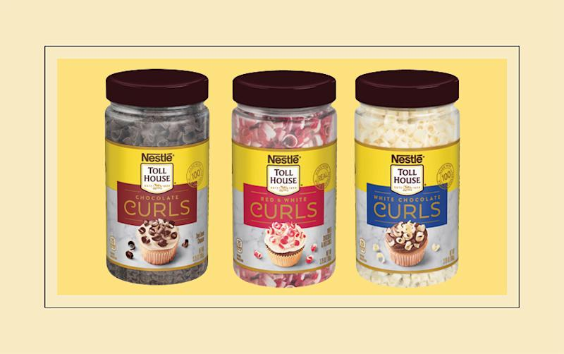 Three containers of Nestle chocolate curls on yellow background