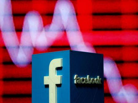 A 3D-printed Facebook logo is seen in front of a displayed stock graph in this illustration taken