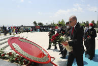 """Turkey's President Recep Tayyip Erdogan and family members of coup victims walk to place flowers by the """"Martyrs Monument"""" outside his presidential palace, in Ankara, Turkey, Wednesday, July 15, 2020. Turkey is marking the fourth anniversary of the July 15 failed coup attempt against the government, with prayers and other events remembering its victims. (Turkish Presidency via AP, Pool)"""