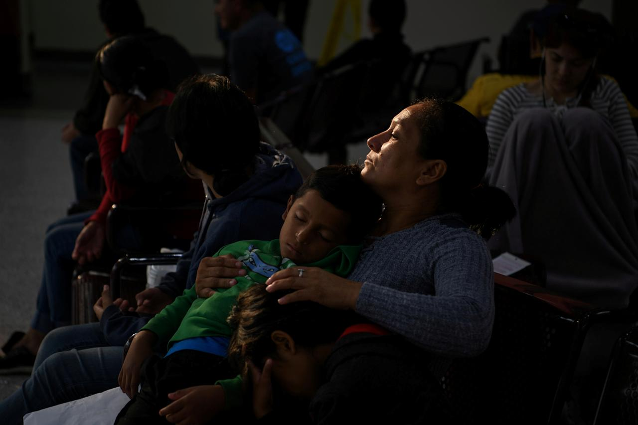 Sonia, an asylum seeker from Honduras, waits with sleeping six-year-old son Yankel and daughter Yarisleidy, twins, before boarding a bus with fellow migrant families recently released from detention at a bus depot in McAllen, Texas, U.S., May 20, 2019.  REUTERS/Loren Elliott     TPX IMAGES OF THE DAY