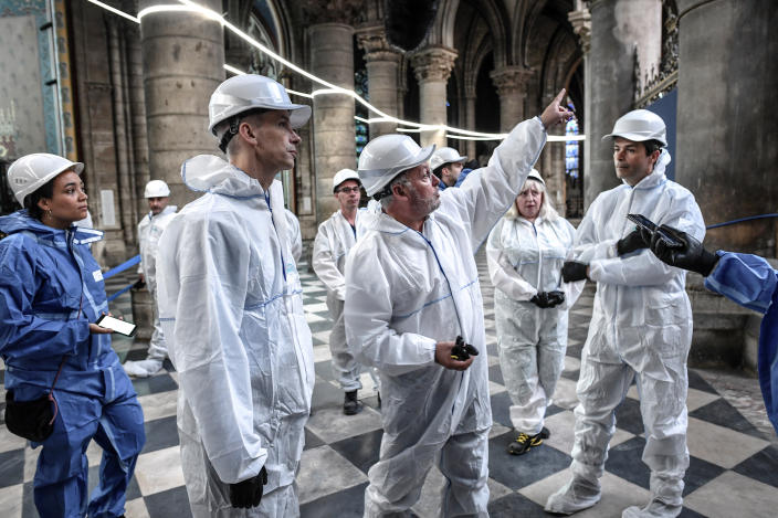 French Culture Minister Franck Riester, second left, listens to French chief architect of historical sites Philippe Villeneuve, center, as they visit the Notre Dame Cathedral three months after a major fire July 17, 2019 in Paris. (Photo: Stephane de Sakutin/Pool via AP)