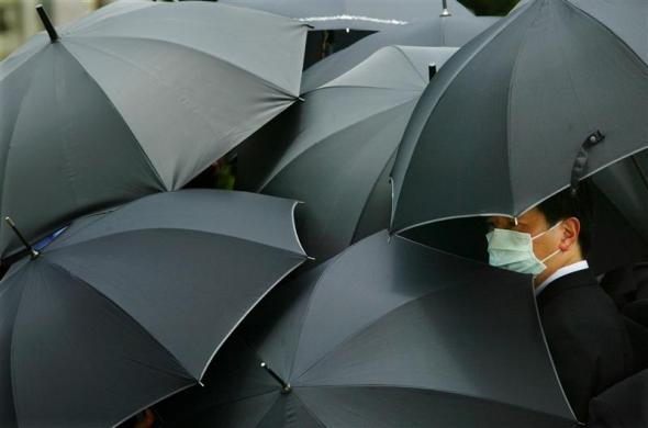 A mourner wearing a mask to ward off SARS hides under an umbrella during the funeral of SARS doctor Tse Yuen-man in Hong Kong May 22, 2003.