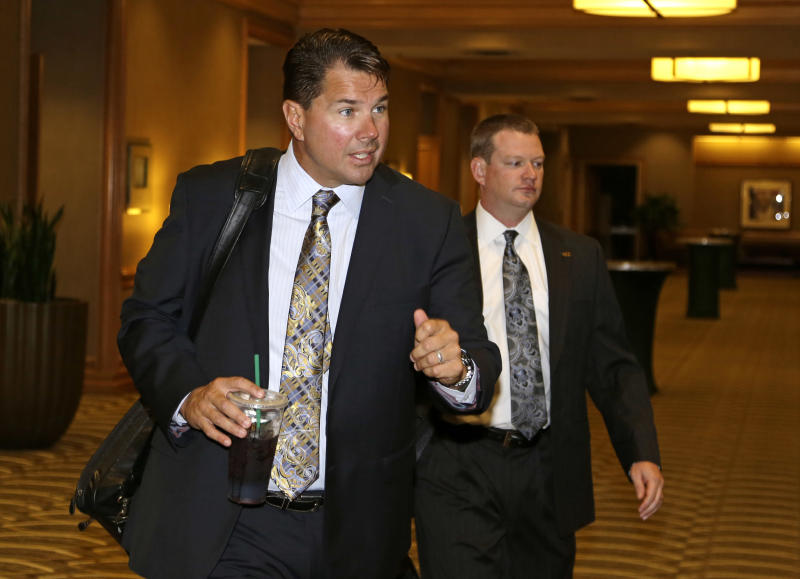 University of Miami football coach Al Golden, left, walks to an NCAA Committee on Infractions hearing in Indianapolis, Thursday, June 13, 2013. The committee is scheduled to open its hearings into allegations the University of Miami committed rules infractions in football and men's basketball. (AP Photo/Michael Conroy)
