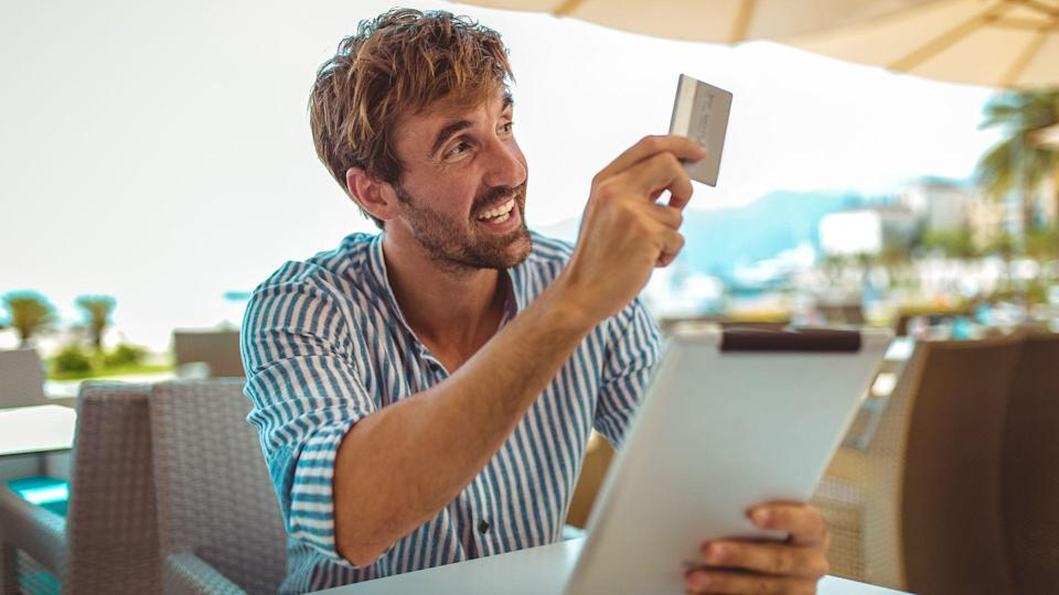 Portrait of cheerful man paying for order with credit card in cafe.
