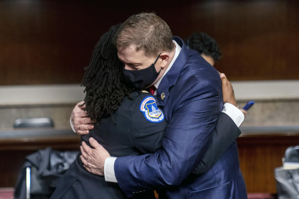 Former U.S. Capitol Police Chief Steven Sund, right, hugs Capitol Police Captain Carneysha Mendoza, left, before they testify before a Senate Homeland Security and Governmental Affairs & Senate Rules and Administration joint hearing on Capitol Hill, Washington, Tuesday, Feb. 23, 2021, to examine the January 6th attack on the Capitol. (AP Photo/Andrew Harnik, Pool)
