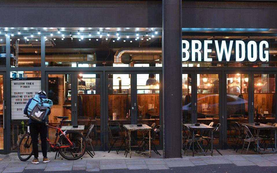 A Deliveroo rider outside an empty Brewdog pub in Liverpool city centre in October 2020 - Asadour Guzelian