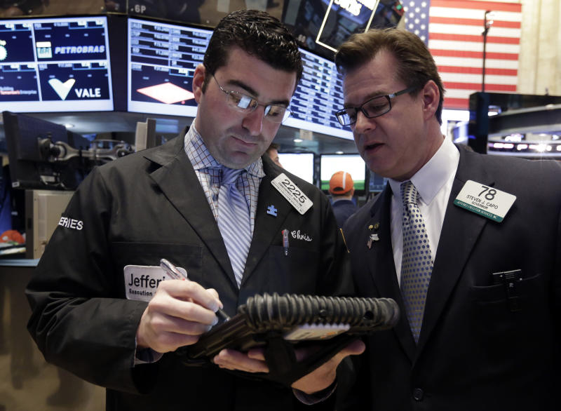 Traders Christopher Anzelone, left, and Steven Capo confer on the floor of the New York Stock Exchange, Friday, April 12, 2013. The stock market is heading lower in early trading after a four-day rise as bank shares weaken. (AP Photo/Richard Drew)