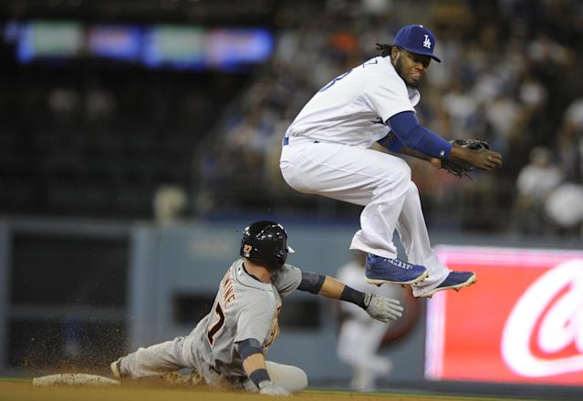Los Angeles Dodgers shortstop Hanley Ramirez, right, jumps to avoid Detroit Tigers' Andrew Romine, left, after he threw to first to complete a double play during the eighth inning of a baseball game in Los Angeles, Tuesday, April 8, 2014. Rajai Davis was out at first. (AP Photo/Kelvin Kuo)