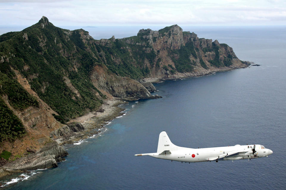 FILE - In this Oct. 13, 2011, file photo, Japan Maritime Self-Defense Force P-3C Orion surveillance plane flies over the disputed islands, called the Senkaku in Japan and Diaoyu in China, in the East China Sea. The Abe government's Defense White Paper 2020 highlights what are potential Chinese and North Korean threats as Japan tries to further increase its defense capability. (Kyodo News via AP, File)