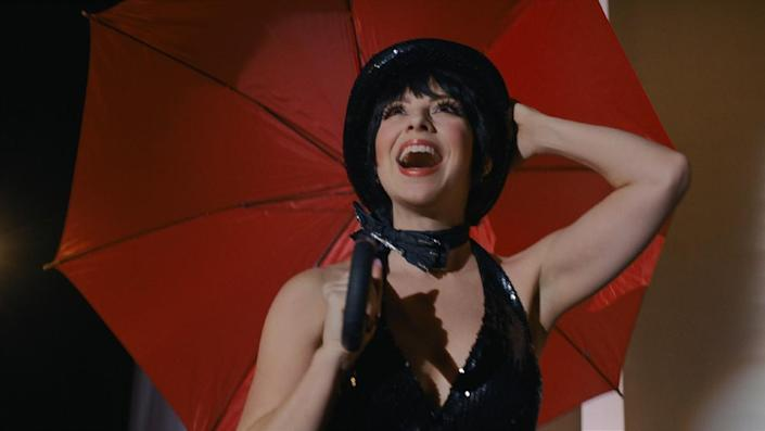 Krysta Rodriguez as Liza Minnelli wearing her iconic top hat and black ensemble from Cabaret in Netflix's Halston.
