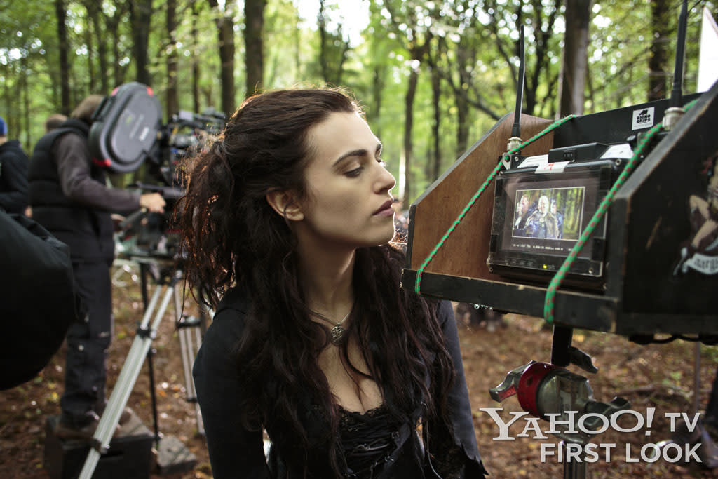 Actress Katie McGrath prepares for a scene by watching a playback monitor in the middle of a forest in Wales.