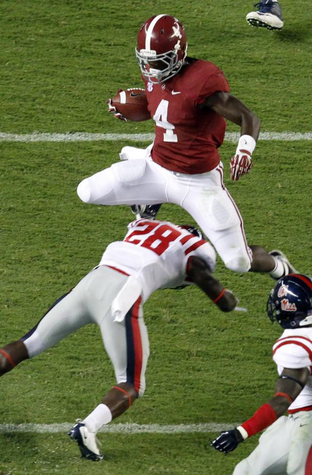Alabama running back T.J. Yeldon (4) hurdles Mississippi defensive back Mike Hilton (28) for a first down during the first half of an NCAA college football game Saturday, Sept. 28, 2013, in Tuscaloosa, Ala. (AP Photo/Butch Dill)