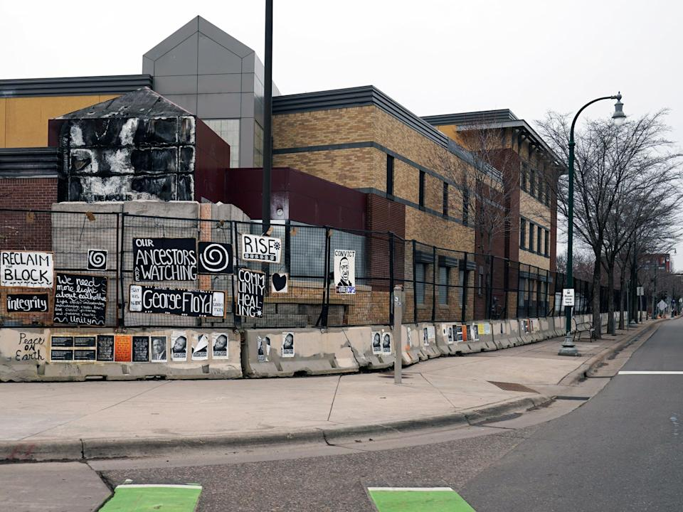 Signs hang on a fence amid the remains of the Minneapolis 3rd Precinct police station that was burned down by protesters 23 March, 2021AP