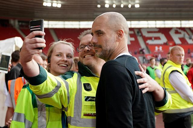 "Soccer Football - Premier League - Southampton vs Manchester City - St Mary's Stadium, Southampton, Britain - May 13, 2018 Manchester City manager Pep Guardiola poses for a photograph with a steward after the match REUTERS/David Klein EDITORIAL USE ONLY. No use with unauthorized audio, video, data, fixture lists, club/league logos or ""live"" services. Online in-match use limited to 75 images, no video emulation. No use in betting, games or single club/league/player publications. Please contact your account representative for further details."