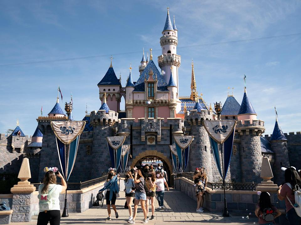 <p>Visitors exit The Sleeping Beauty Castle at Disneyland in Anaheim, California on 30 April 2021</p> (AP)