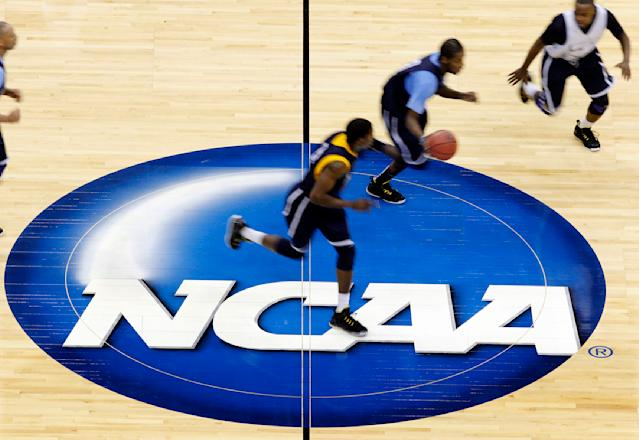 "FILE - In this March 24, 2011, file photo, Marquette players are blurred by a slow shutter speed as they run the ball up the court during practice in Newark, N.J., for an East regional semifinal game in the NCAA college basketball tournament. Bank records and other expense reports that are part of a federal probe into college basketball list a wide range of impermissible payments from agents to at least two dozen players or their relatives, according to documents obtained by Yahoo Sports. NCAA president Mark Emmert said in a statement Friday, Feb. 23, 2018, the allegations ""if true, point to systematic failures that must be fixed and fixed now if we want college sports in America.""(AP Photo/Mel Evans, File)"