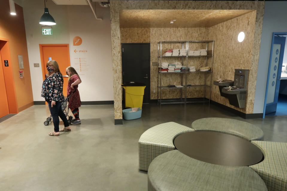 Connie Wade, left, waits for an elevator with her daughter Emilyanne, 12, Wednesday, June 17, 2020, in a common area of Mary's Place, a family homeless shelter located inside an Amazon corporate building on the tech giant's Seattle campus. The facility is home to the Popsicle Place shelter program, an initiative to address the needs of homeless children with life-threatening health conditions. (AP Photo/Ted S. Warren)