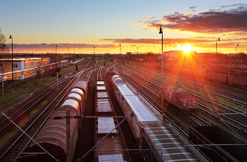 Trains at a rail station with the sun setting in the background.