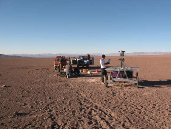The Zoë rover being checked out at the start of its Atacama Desert traverse in June 2013. In the background are the two 4x4 trucks that were used to follow the robot. The engineers stay within communication range to monitor the robot but try to