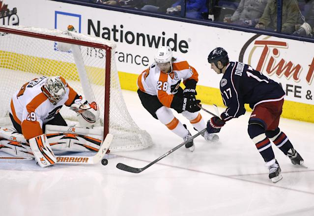 Columbus Blue Jackets' Brandon Dubinsky (17) shoots against Philadelphia Flyers goalie Ray Emery (29) as Flyers' Claude Giroux (28) tries to help during the third period of an NHL hockey game on Saturday, Dec. 21, 2013, in Columbus, Ohio. Columbus won 6-3. (AP Photo/Mike Munden)