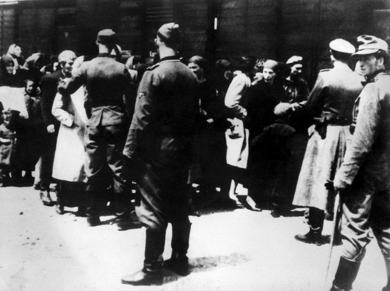 SS soldiers lead newly arrived prisoners to the gas chambers at the Auschwitz concentration camp