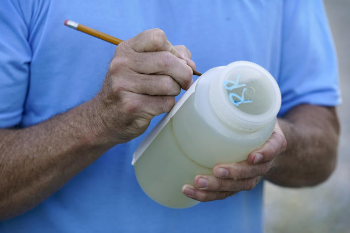 Des Moines Water Works employee Bill Blubaugh marks a water sample collected from the Raccoon River, Thursday, June 3, 2021, in Des Moines, Iowa. Each day the utility analyzes samples from the Raccoon River and others from the nearby Des Moines River as it works to deliver drinking water to more than 500,000 people in Iowa's capital city and its suburbs. (AP Photo/Charlie Neibergall)