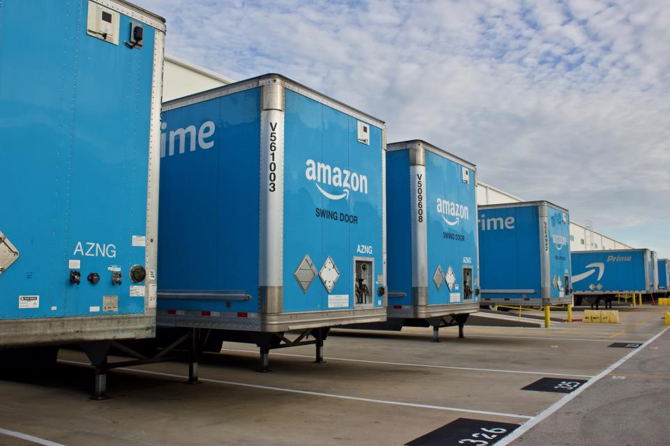 Multiple blue Amazon Prime trailers backed into bays at a distribution center to unload products for area customers. (Photo: Getty)