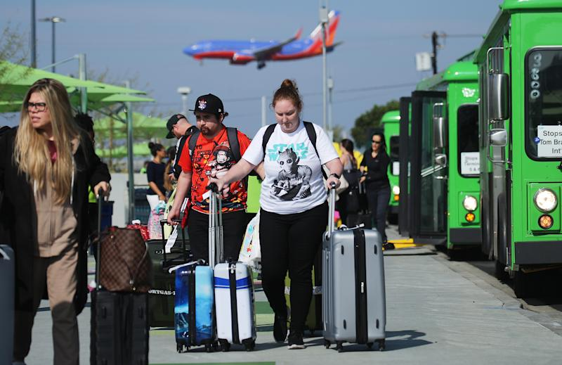LOS ANGELES, CALIFORNIA - NOVEMBER 06: Arriving passengers walk with their luggage as they prepare to board vehicles at the new 'LAX-it' ride-hail passenger pickup lot at Los Angeles International Airport (LAX) on November 6, 2019 in Los Angeles, California. The airport has instituted a ban on Lyft, Uber and taxi curbside pickups as airport construction increases during a modernization program. Passengers have complained of long wait times and confusion at the pickup area, especially during peak hours. Passengers must depart their terminal and then ride a shuttle bus or walk to the separate pickup lot. (Photo by Mario Tama/Getty Images)