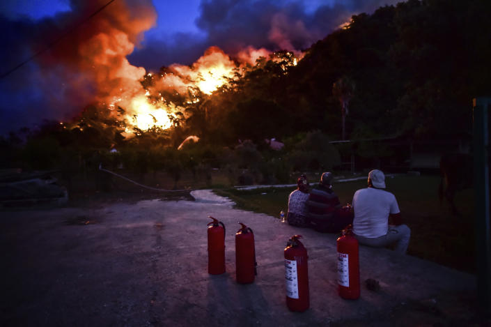 People watch before they leave as advancing fires rage Hisaronu area, Turkey, Monday, Aug. 2, 2021. For the sixth straight day, Turkish firefighters battled Monday to control the blazes that are tearing through forests near Turkey's beach destinations. Fed by strong winds and scorching temperatures, the fires that began Wednesday have left eight people dead. Residents and tourists have fled vacation resorts in flotillas of small boats or convoys of cars and trucks. (AP Photo)