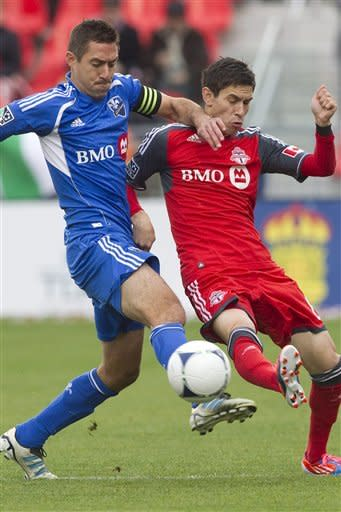 Toronto FC 's Eric Avila, right, battles for the ball with Montreal Impact's Davy Arnaud during first half MLS action in Toronto on Saturday Oct. 20, 2012. (AP Photo/ The Canadian Press, Chris Young)