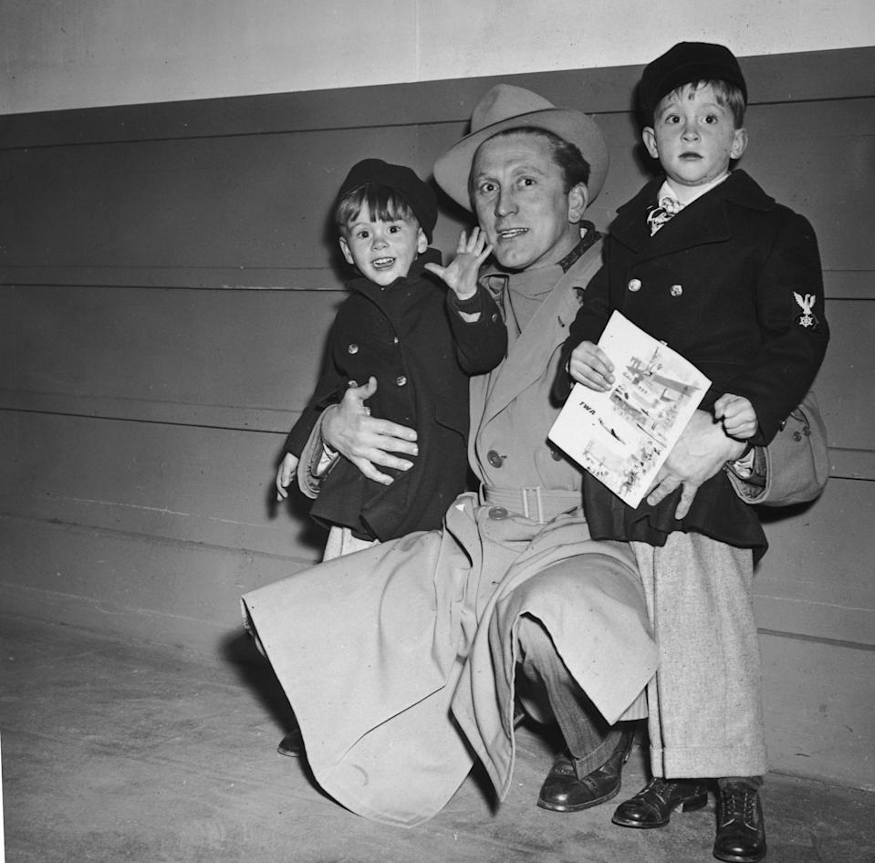 circa 1955:  American actor Kirk Douglas kneels beside his sons, Joel (L) and Michael (future actors).  All three wear winter coats.  Michael is carrying a comic book.  (Photo by Hulton Archive/Getty Images)