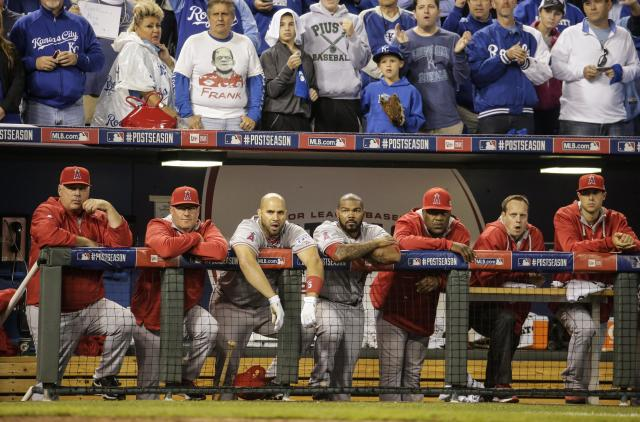 Los Angeles Angels manager Mike Scioscia, left, and players follow the ninth inning of Game 3 of baseball's AL Division Series in Kansas City, Mo., Sunday, Oct. 5, 2014. The Kansas City Royals defeated the Los Angeles Angels 8-3 to sweep the series. (AP Photo/Charlie Riedel)