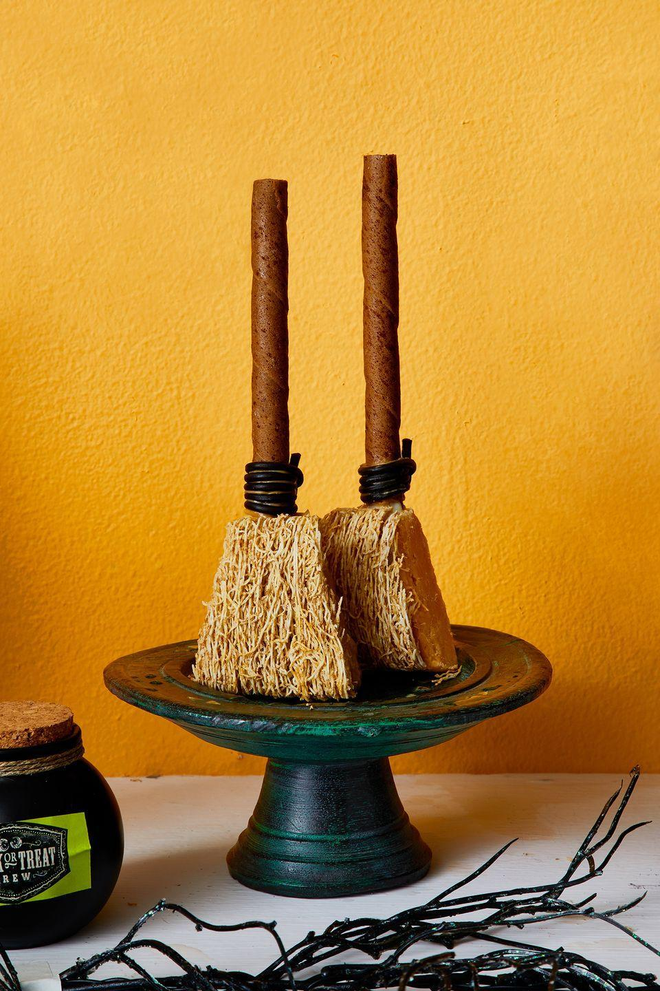 """<p>Boost your Halloween table's visual appeal with these mini fudge broomsticks that are almost too cute to eat. </p><p><a class=""""link rapid-noclick-resp"""" href=""""https://go.redirectingat.com?id=74968X1596630&url=https%3A%2F%2Fwww.walmart.com%2Fip%2FHERSHEY-S-Hot-Fudge-Topping-Baking-Supplies-12-8-oz-Jar%2F20702794&sref=https%3A%2F%2Fwww.goodhousekeeping.com%2Fholidays%2Fhalloween-ideas%2Fg33437890%2Fhalloween-table-decorations-centerpieces%2F"""" rel=""""nofollow noopener"""" target=""""_blank"""" data-ylk=""""slk:SHOP FUDGE"""">SHOP FUDGE</a></p>"""
