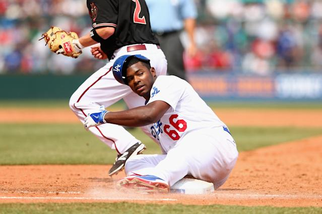 SYDNEY, AUSTRALIA - MARCH 23: Yasiel Puig of the Dodgers is tagged out sliding back to first base during the MLB match between the Los Angeles Dodgers and the Arizona Diamondbacks at Sydney Cricket Ground on March 23, 2014 in Sydney, Australia. (Photo by Cameron Spencer/Getty Images)