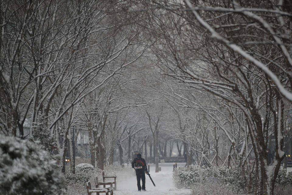 A man clears the snow at a park in Goyang, South Korea, Tuesday, Jan. 12, 2021. (AP Photo/Lee Jin-man)